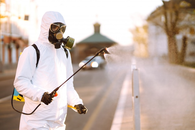 A man wearing special protective disinfection suit sprays sterilizer in the empty public place at dawn in the city of quarantine. covid -19. cleaning concept.