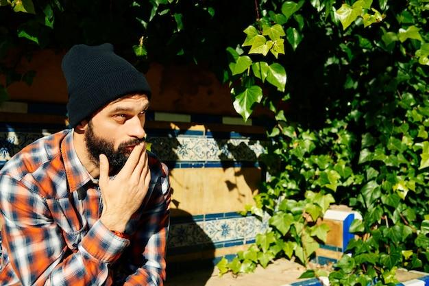 Человек в полосатой рубашке и шляпе, сидя на скамейке