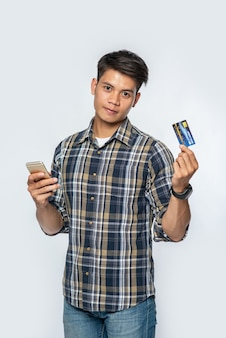 A man wearing a striped shirt holds a credit card and smartphone