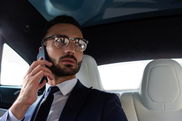 Человек в костюме. красивый бородатый мужчина в костюме звонит секретарю, сидя в своей машине