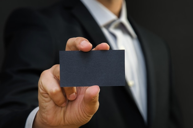 Man wearing a suit holding white business card on black wall surface.