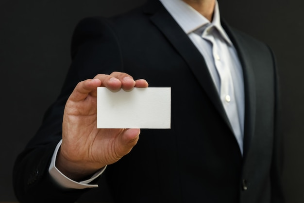 Man wearing a suit holding white business card.