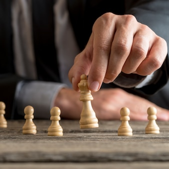 Man wearing suit moving the queen piece lifting it up in his fingers in a close up view with pawns visible behind on the desk.