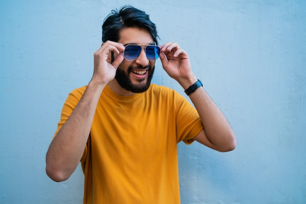 Man wearing summer clothes and sunglasses.