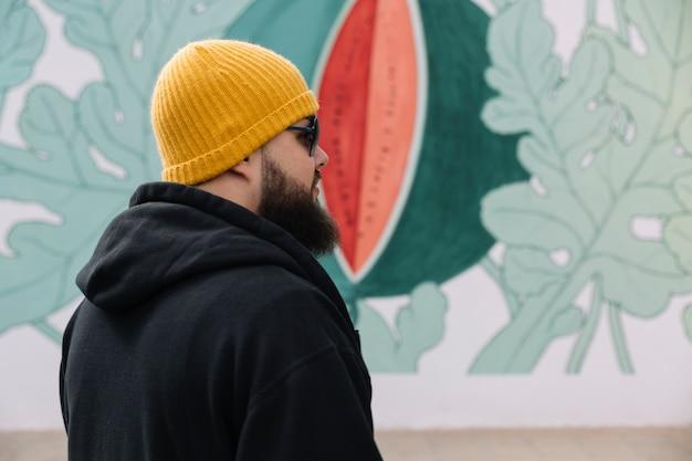 Uomo che indossa occhiali da sole e cappello a maglia in piedi davanti al muro dipinto