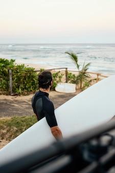 Человек в одежде серфера и держит доску для серфинга