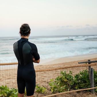 サーファーの服を着て海を見ている男