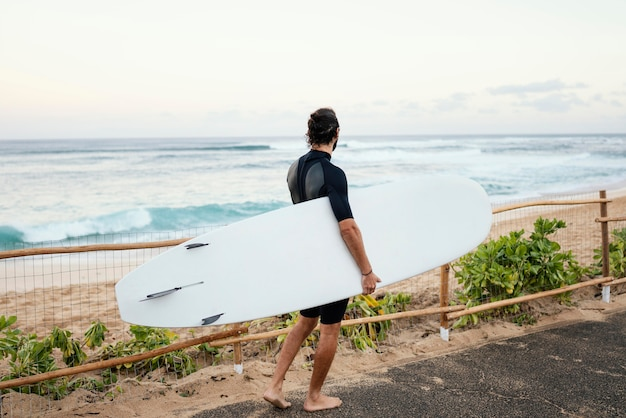 Man wearing surfer clothes and holding his surfboard long shot