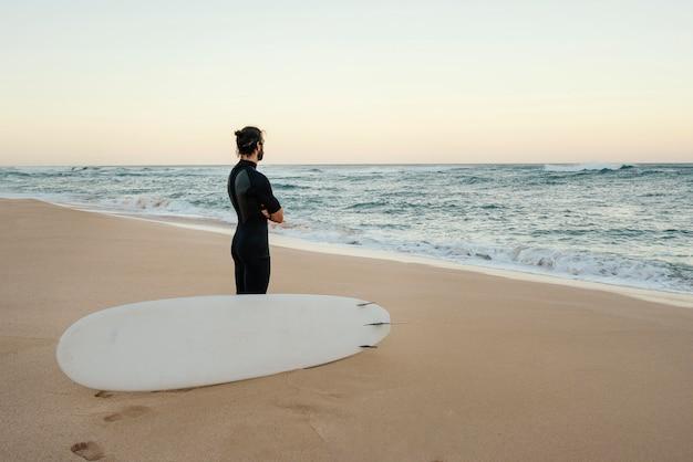 Человек в одежде серфера смотрит на восход солнца
