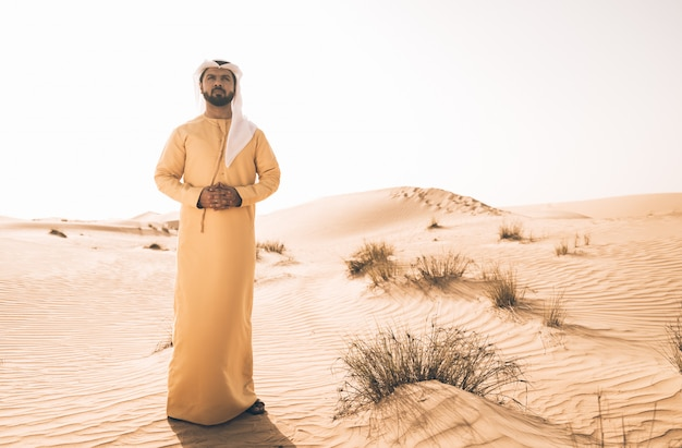 砂漠で過ごす伝統的なアラブ首長国連邦の服を着た男