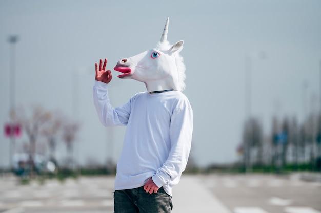 손으로 확인 제스처를 만드는 유니콘 마스크를 착용하는 남자
