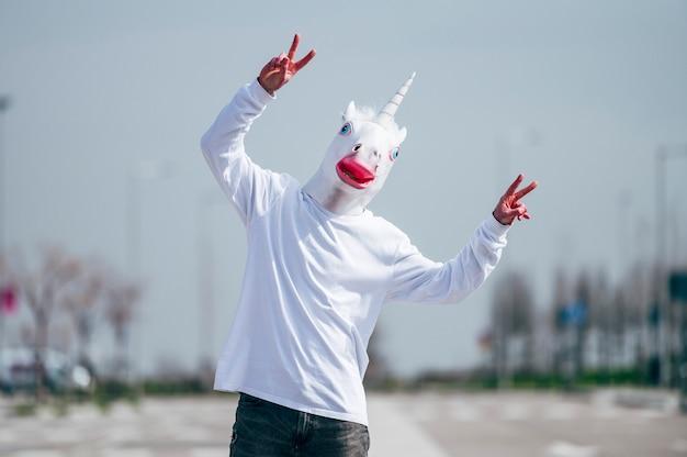 손가락으로 승리 제스처를 만드는 유니콘 마스크를 착용하는 남자