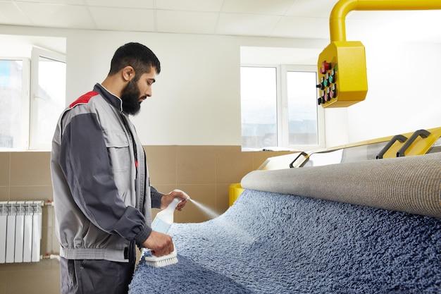 Мужчина в униформе распыляет моющее средство на синем ковре, чтобы удалить пятно при профессиональной уборке