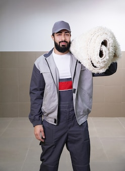Man wearing uniform standing with a roll of carpet on his shoulder