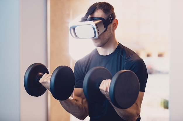 Man wearing virtual reality glasses with dumbbells