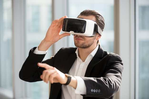 Man wearing vr headset and pointing at the air