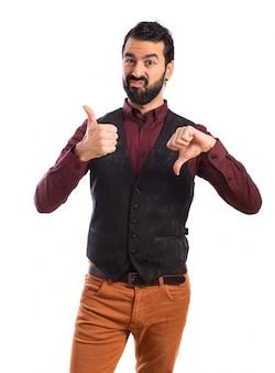 Man wearing waistcoat making a good-bad sign