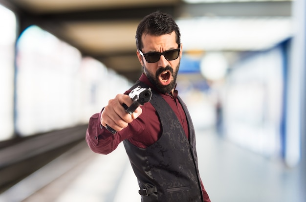 Man wearing waistcoat shooting with a pistol  on unfocused background