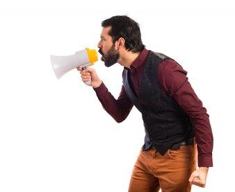 Man wearing waistcoat shouting by megaphone