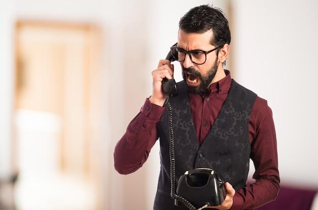 Man wearing waistcoat talking to vintage phone  on unfocused background