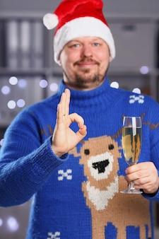 Человек, носящий теплый синий свитер с оленями, держит в руке шампанское