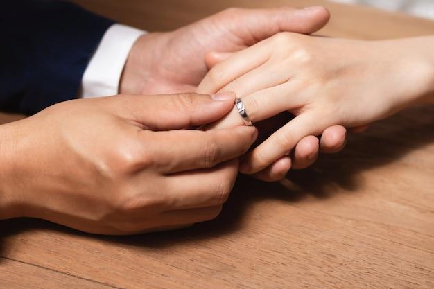 Man wearing the wedding ring to woman finger.