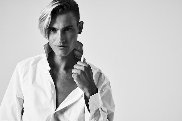 Человек в белой рубашке модная прическа позирует в элегантном стиле студии