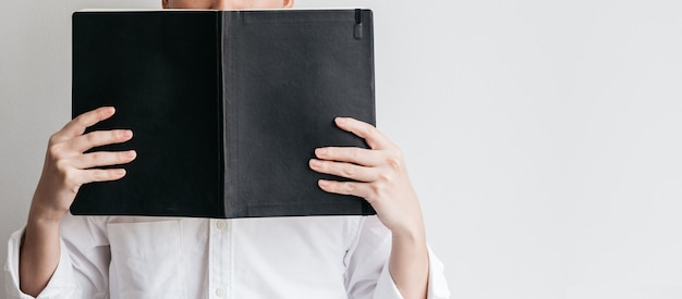 Man wearing white shirt and holding a black cover book in front of him.