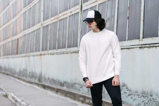 Man wearing white sweatshirt or hoodie, baseball cap and glasses outside on the city streets.