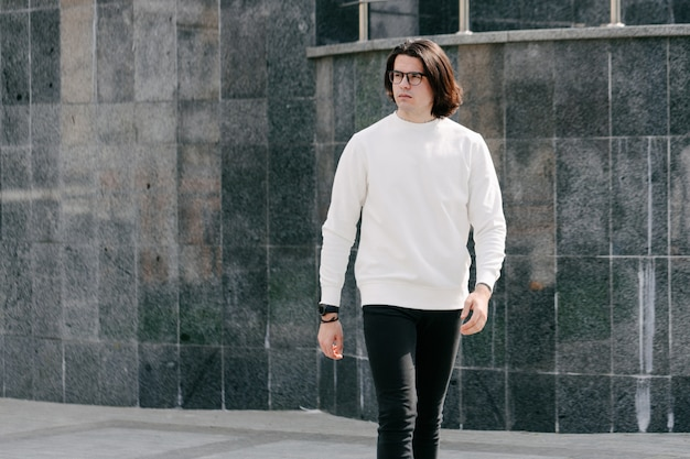 Man wearing white sweatshirt or hoodie and glasses outside on the city streets.