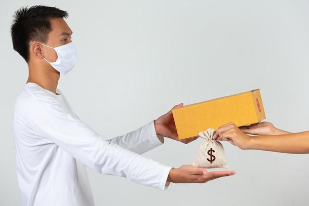 Un uomo che indossa una maglietta bianca tiene in mano una cassetta postale marrone per consegnare le cose. fai gesti ed espressioni facciali.