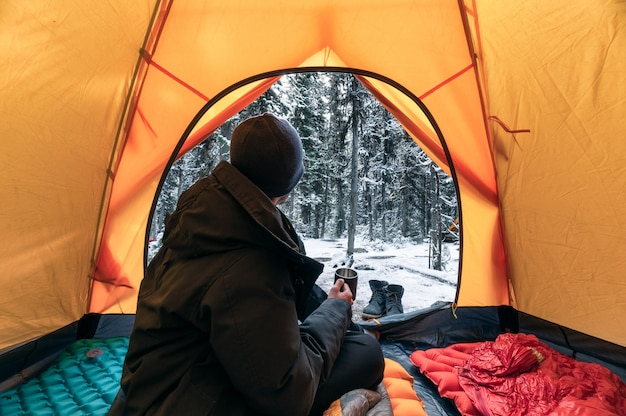 Man wearing winter coat sitting and holding a coffee cup in orange tent on campsite