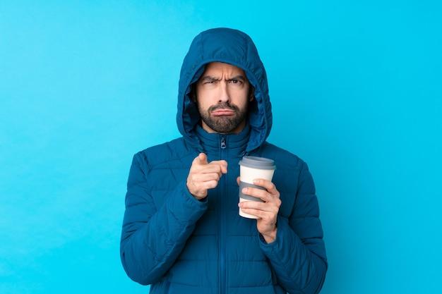 冬のジャケットを着て、欲求不満と前を指している孤立した青い壁にテイクアウトのコーヒーを保持している男