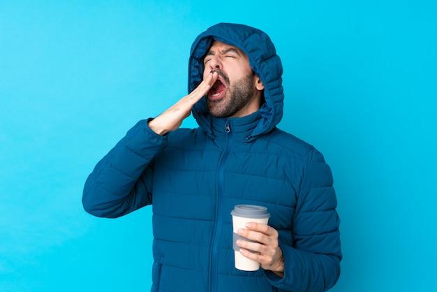 남자 겨울 자 켓을 착용 하 고 격리 된 파란색 벽 하 품을 통해 테이크 아웃 커피를 들고 손으로 활짝 열려 입을 덮고