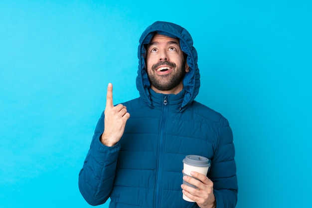 Man wearing winter jacket and holding a takeaway coffee over isolated blue wall pointing up and surprised