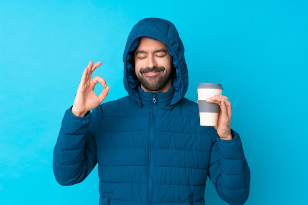 Man wearing winter jacket and holding a takeaway coffee over isolated blue wall in zen pose
