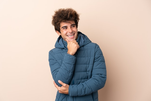 Man wearing winter jacket over isolated wall looking side