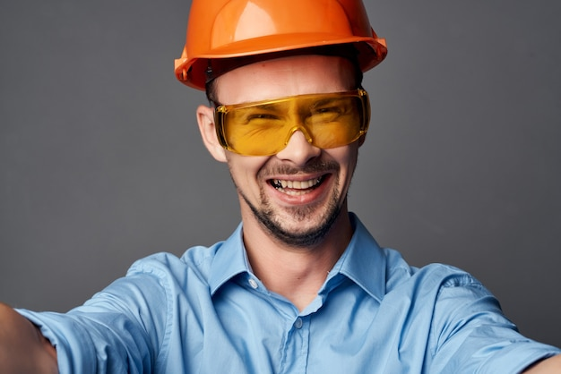 Человек в желтых очках с оранжевой краской.