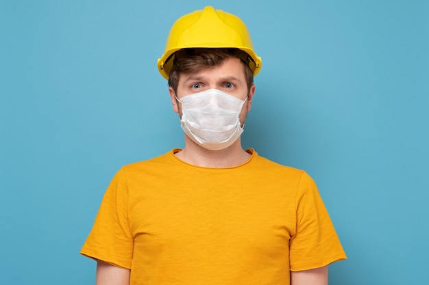 Man wearing a yellow hard hat and medical mask during quarantine