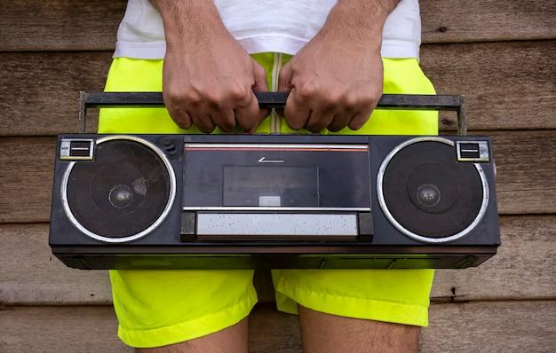 古いラジオを持っている黄色いズボンを着ている男