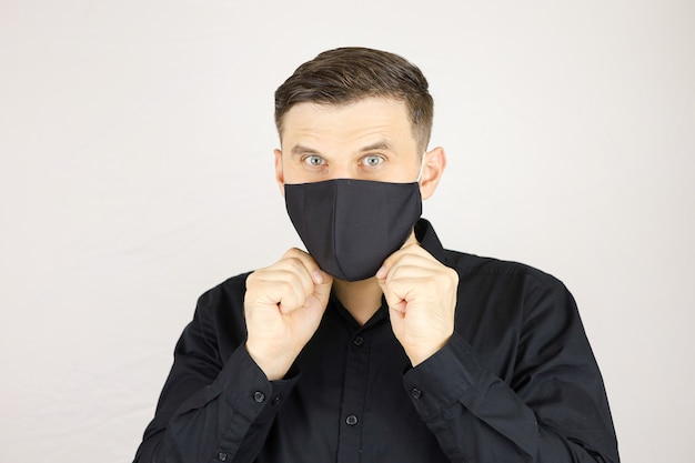 The man wears a black medical mask  on a white background