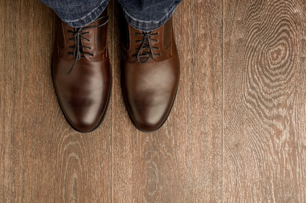 The man wears brown classic shoes on wooden flour.