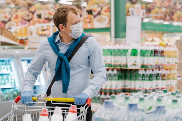 Man wears disposable medical mask and rubber gloves, stands in supermarket with trolley, makes shopping
