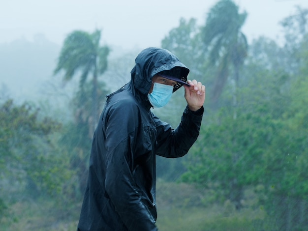Man wears face mask and raincoat under heavy tropical rain. tropical environment.