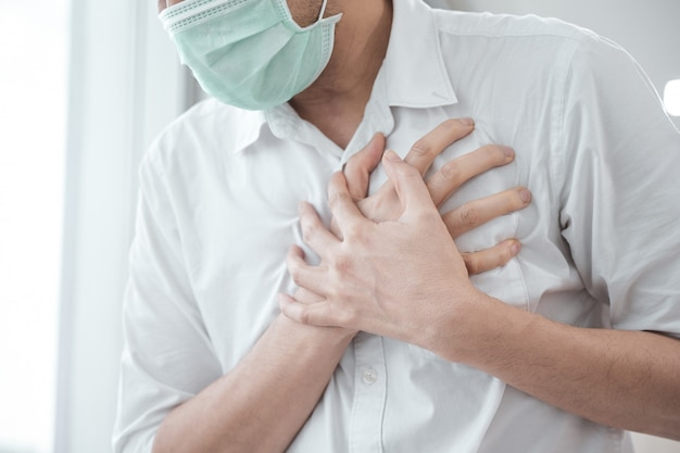 남자는 의료 얼굴 마스크를 착용하고 가슴 통증을 느낀다