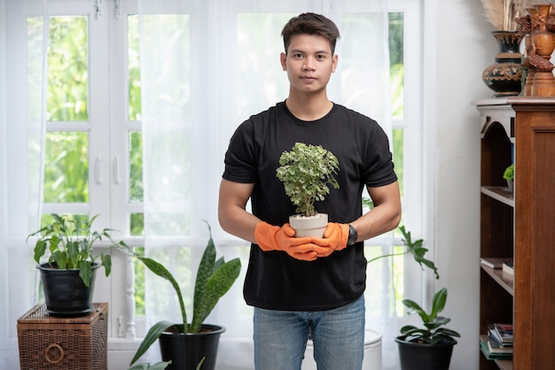 A man wears orange gloves and stands to hold a plant pot in the house.