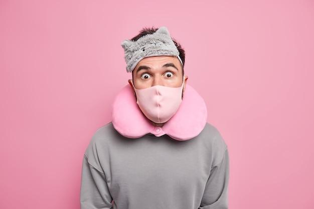 男性はコロナウイルスに対する保護マスクを着用し、カジュアルな服装の車で旅行中に首枕とスリープマスクを使用します