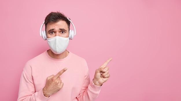 Человек в защитной маске указывает на пустое место, слушает аудиозапись в наушниках, одет в повседневный свитер, дает рекомендации по карантинным мерам.