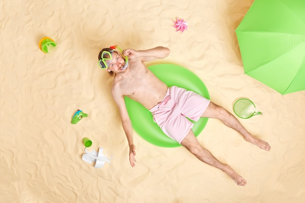 Man wears snorkeling mask shorts poses on inflated swimring enjoys nice summer holidays relaxes near sea hides from sun under parasol