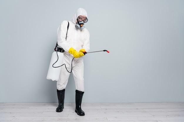 Мужчина носит специальный защитный костюм и маску